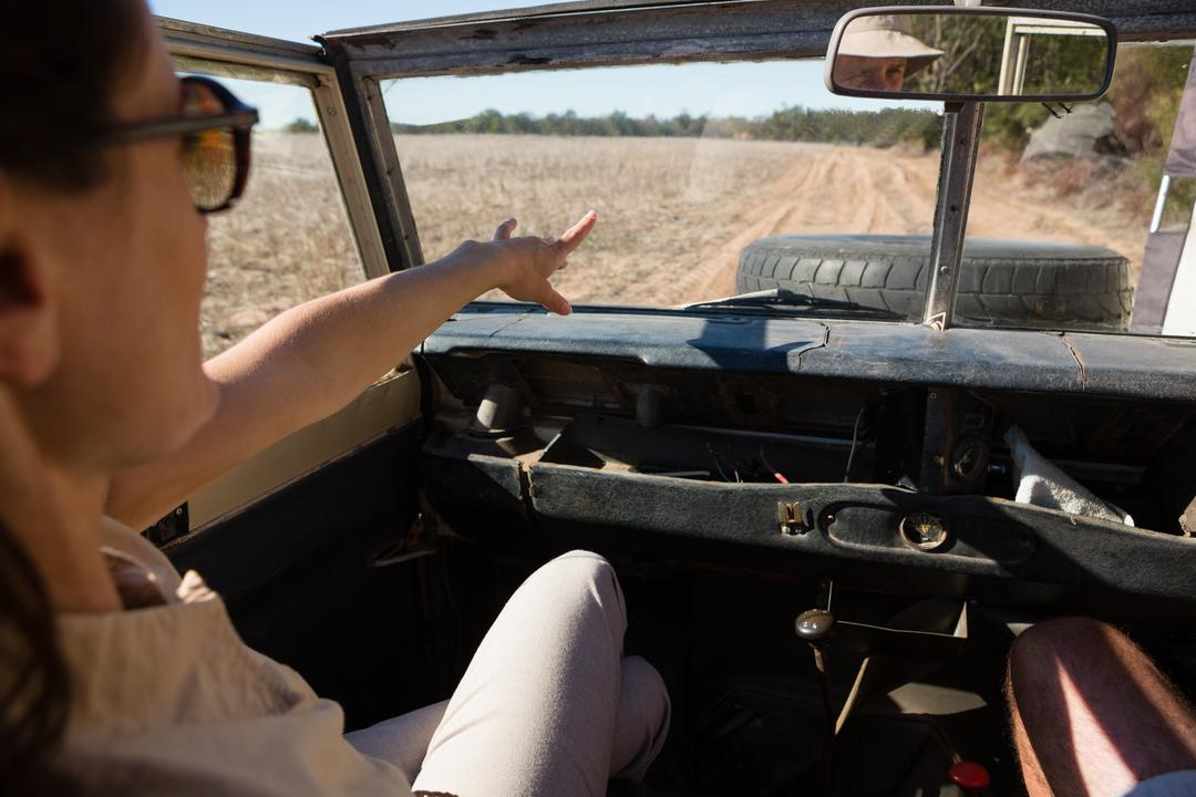 Woman pointing while traveling in off road vehicle on landscape