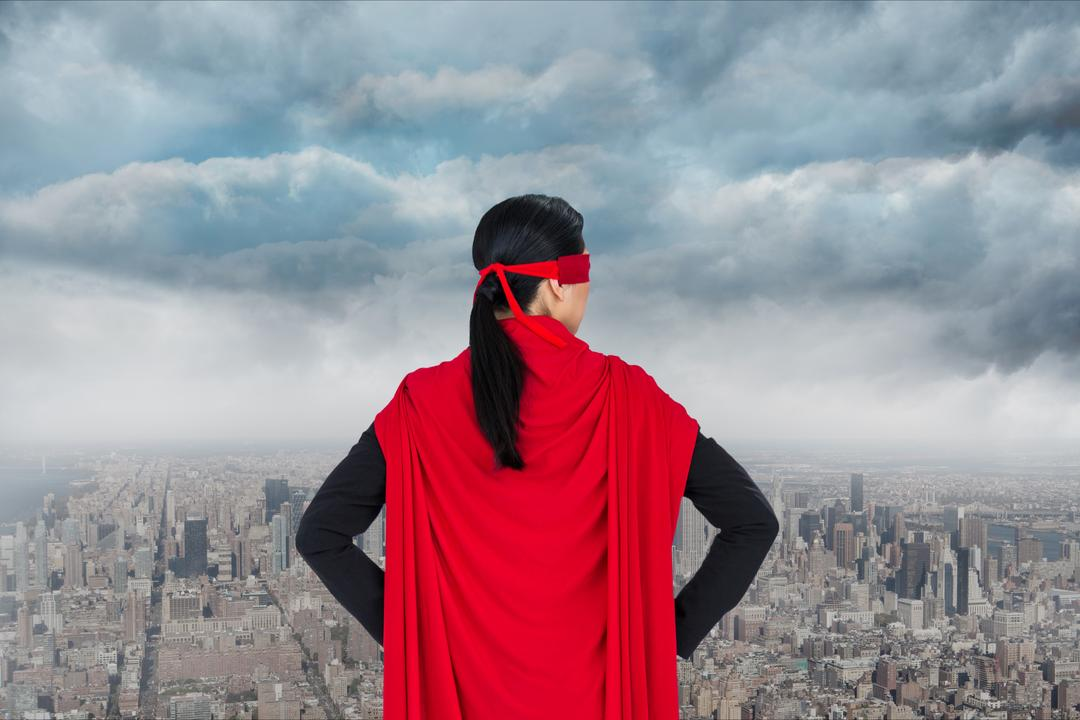 Digital composite of Businesswoman in super hero costume looking at buildings