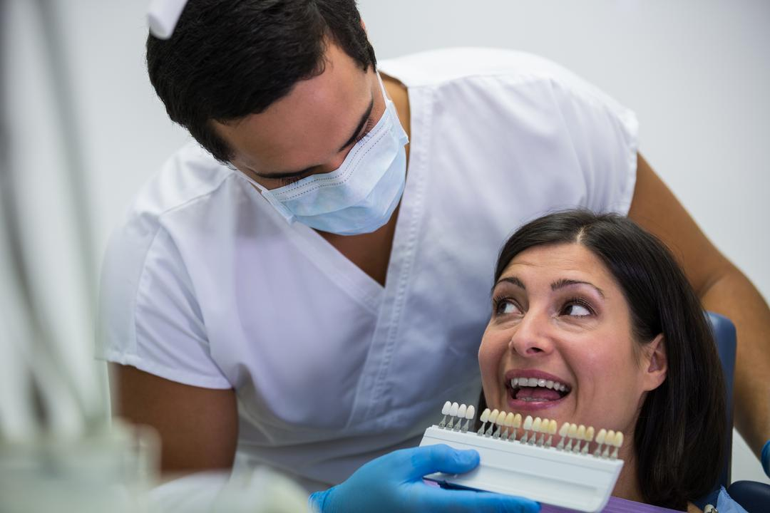 Dentist examining female patient with teeth shades at dental clinic Free Stock Images from PikWizard
