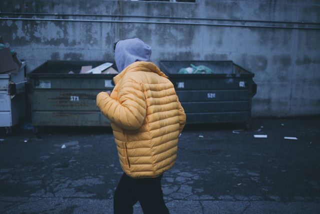 Man in front of dumpsters wearing yellow jacket