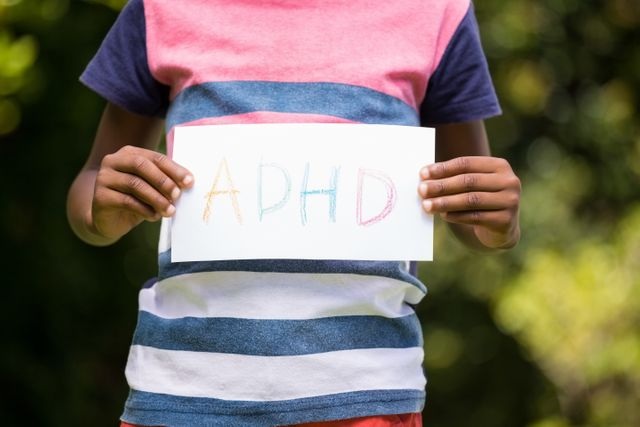 Boy showing a poster with ADHD in the park