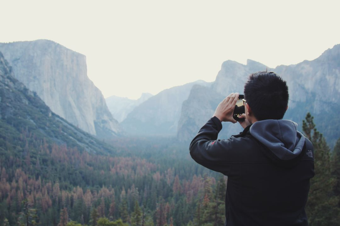 Male taking a photograph of landscape background with mobile phone