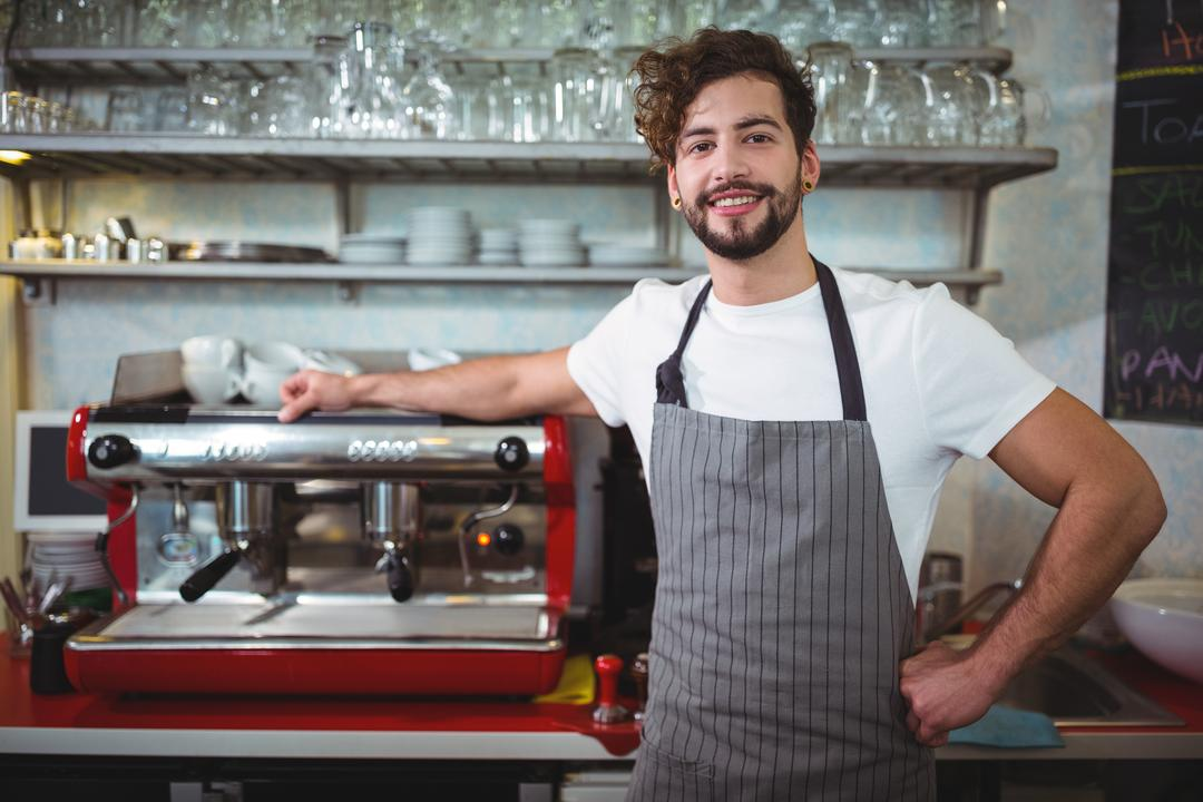 Portrait of smiling waiter standing with hand on hip at counter in café
