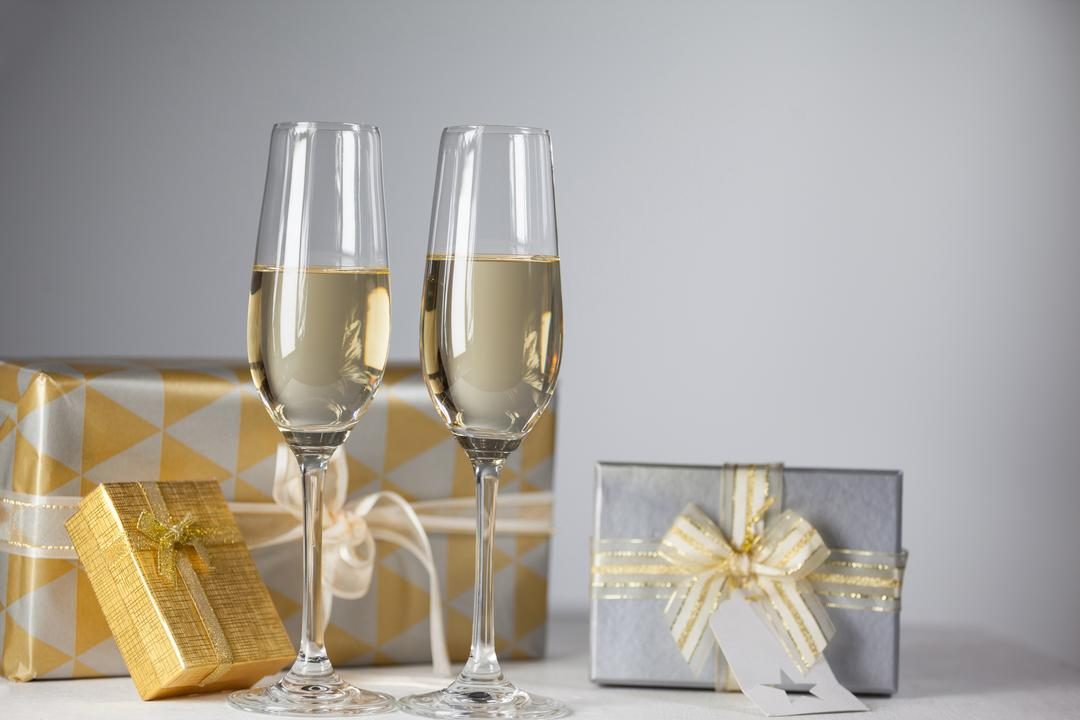 Two champagne flutes and Christmas gifts against white background