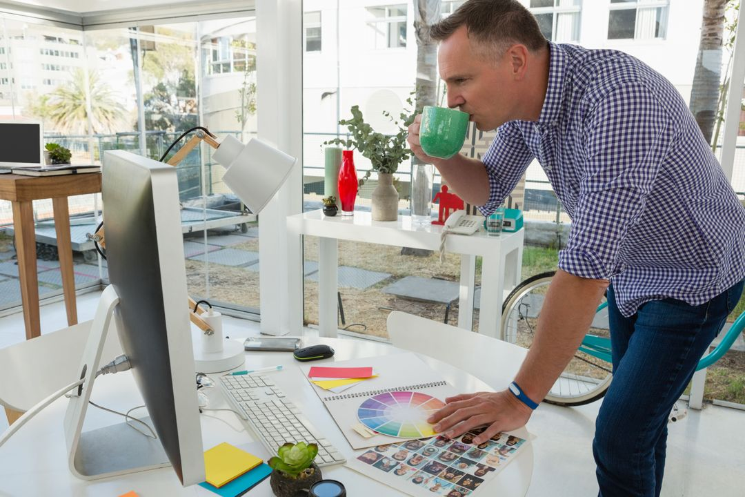 Designer looking at a desktop while drinking coffee with color charts on the desk