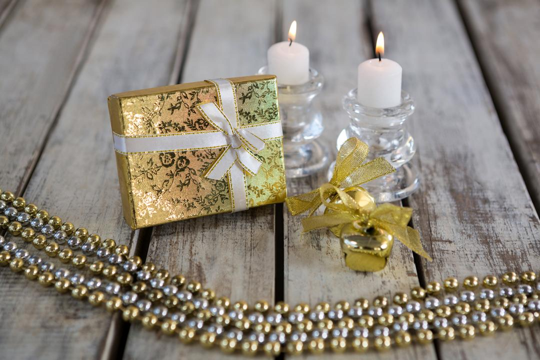 Lit candle and wrapped gift on wooden plank during christmas time