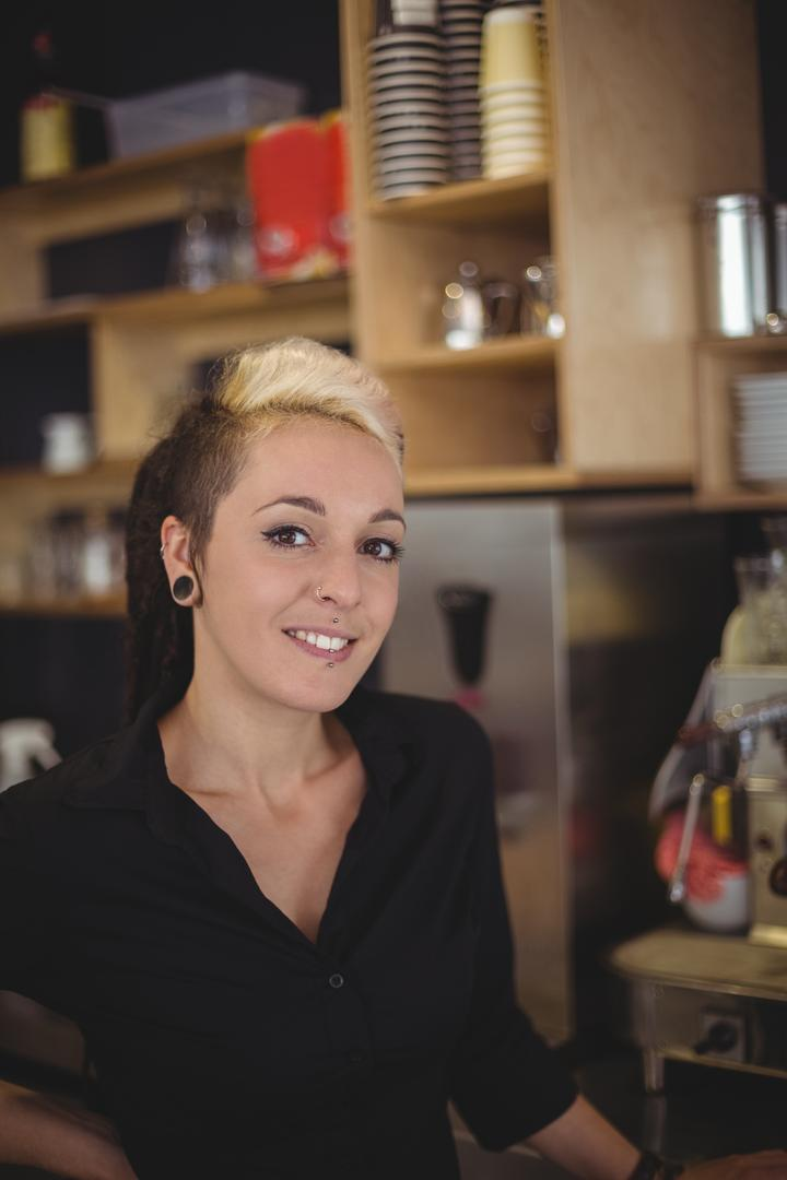 Portrait of smiling waitress standing with hands on hips in café