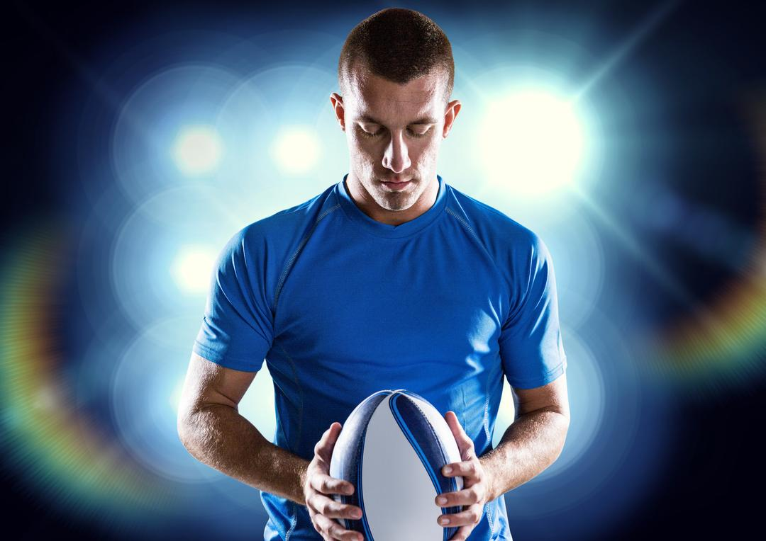 Determined rugby player holding ball against illuminated background