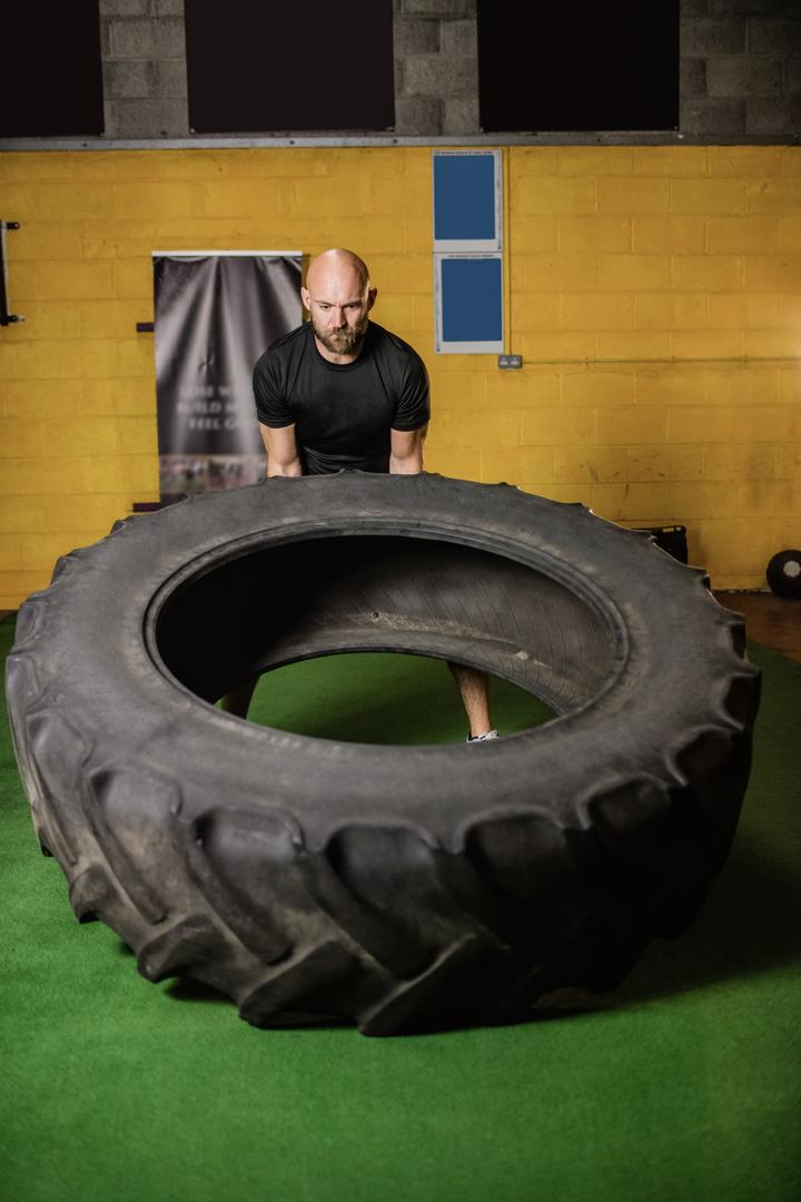 Thai boxer lifting heavy tyre in the fitness studio