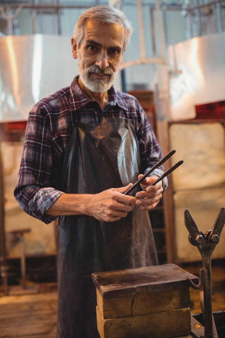 Portrait of glassblower holding tongs at glassblowing factory