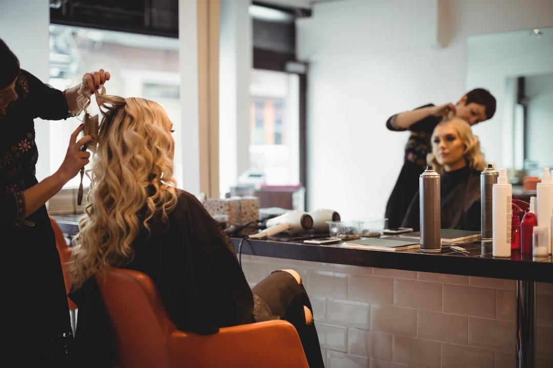 Female hairdresser styling clients hair in saloon
