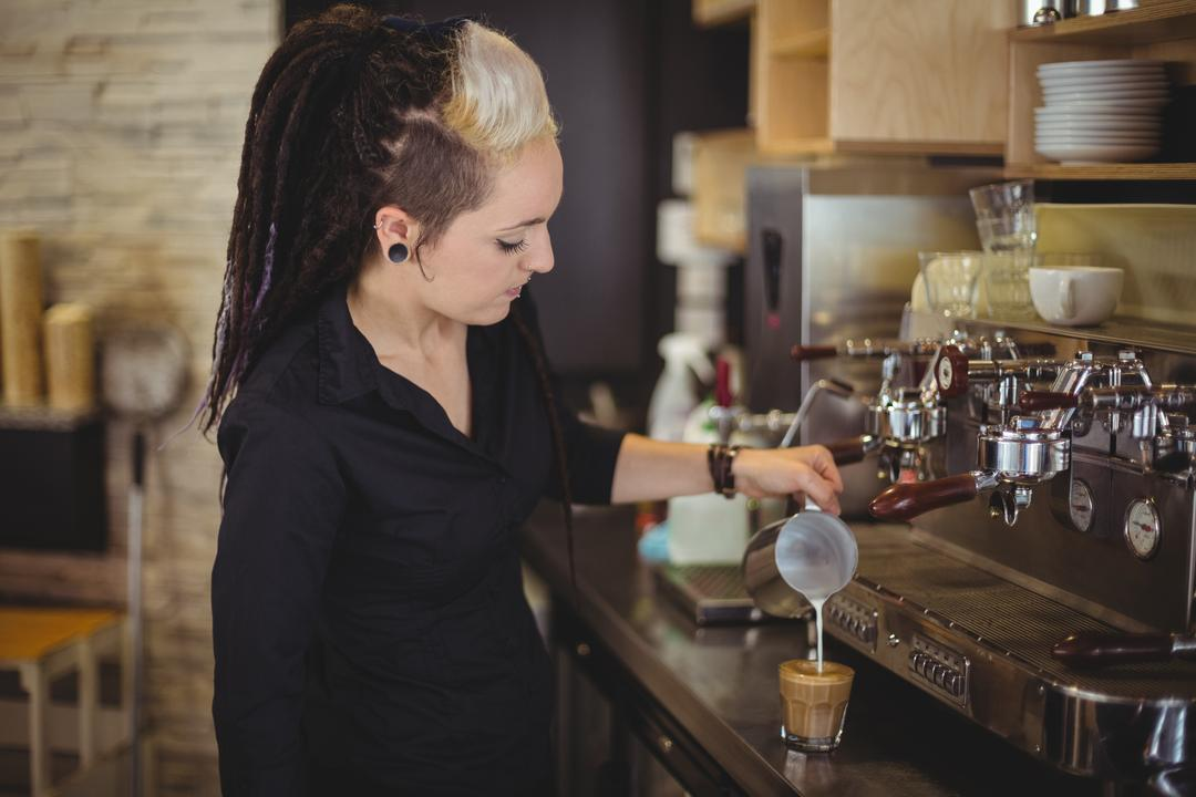 Waitress pouring milk into coffee cup at counter in cafe