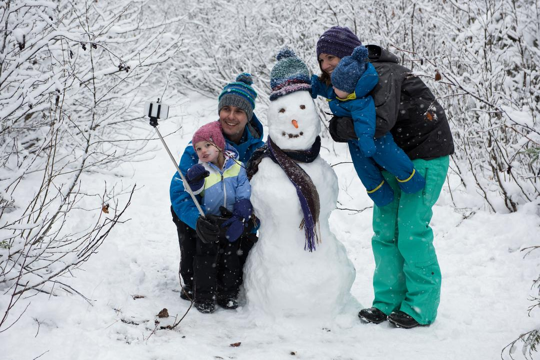 Family taking selfie with snowman on beautiful snowy day