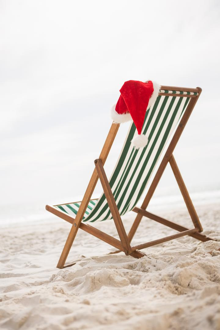 Santa hat kept on empty beach chair at tropical sand beach Free Stock Images from PikWizard