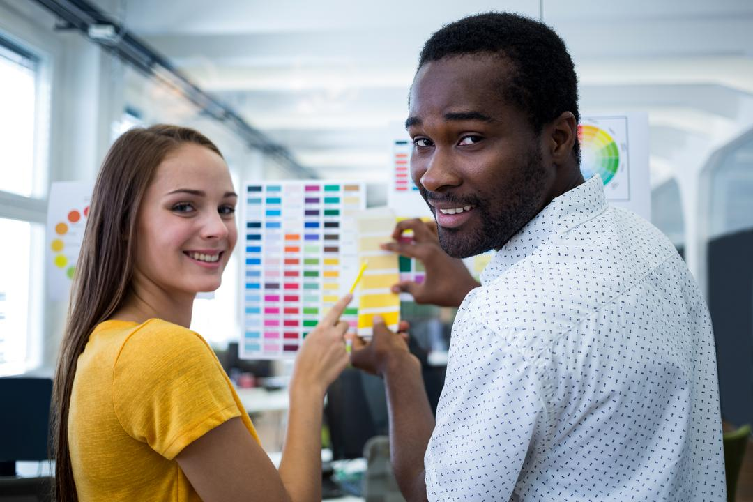 Male and female graphic designers interacting over color chart in office Free Stock Images from PikWizard