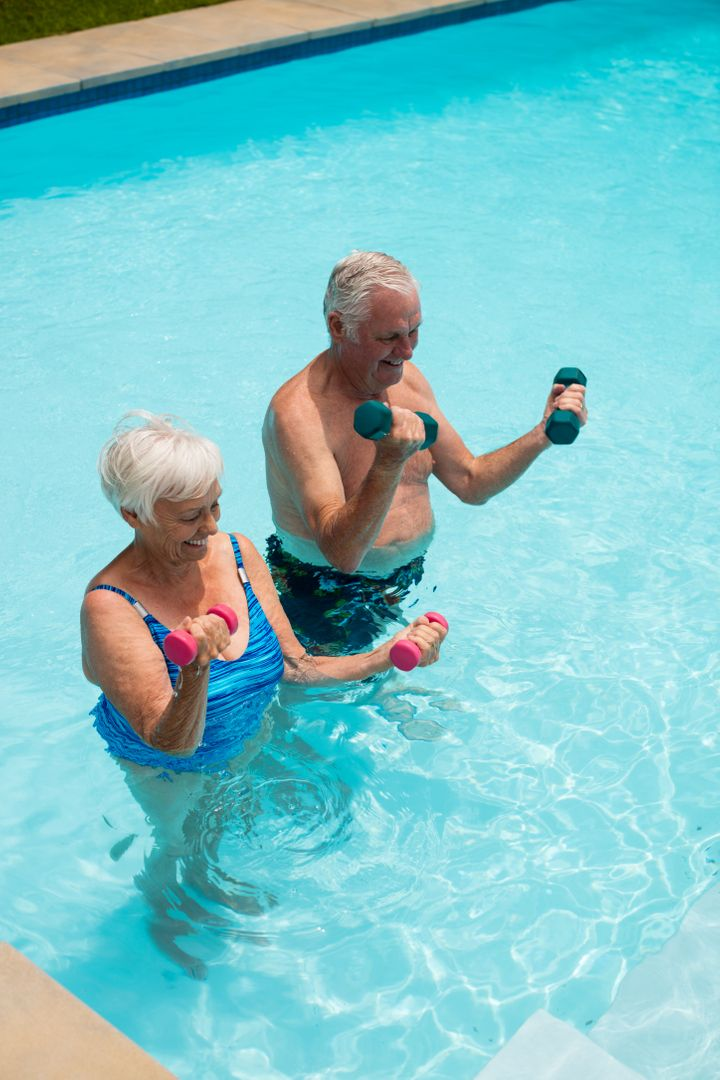 Happy senior couple exercising with dumbbells in the pool Free Stock Images from PikWizard
