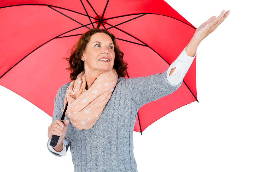 Mature woman holding red umbrella while standing against white background Free Stock Images from PikWizard