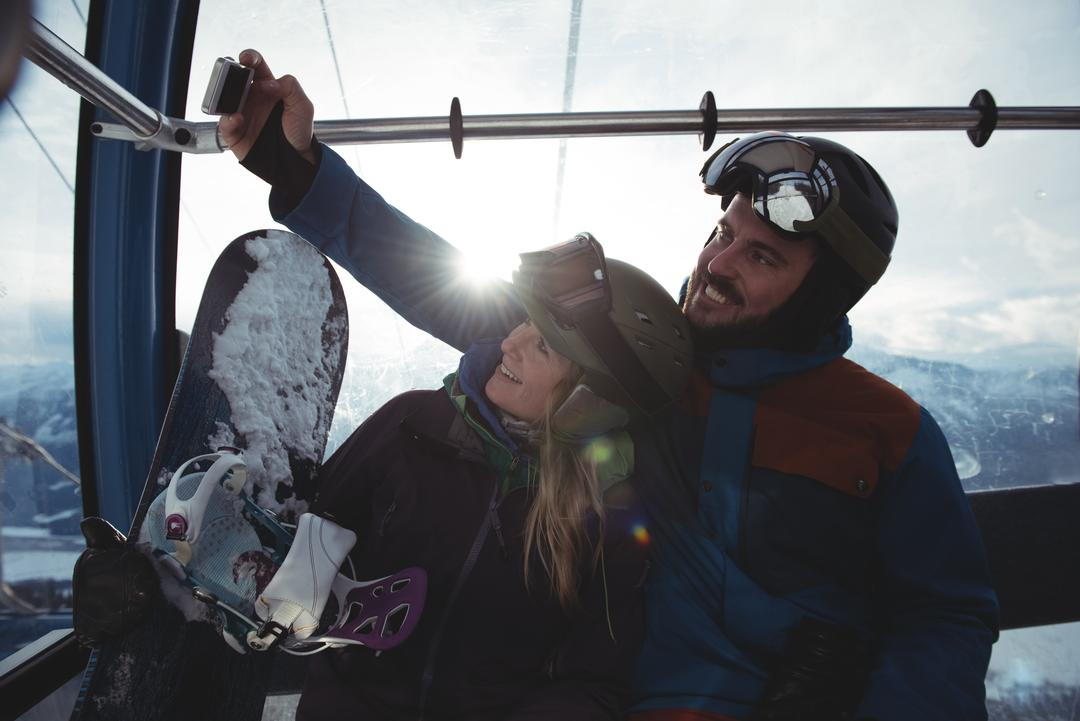 Happy couple taking selfie in overhead cable car against sky during winter Free Stock Images from PikWizard