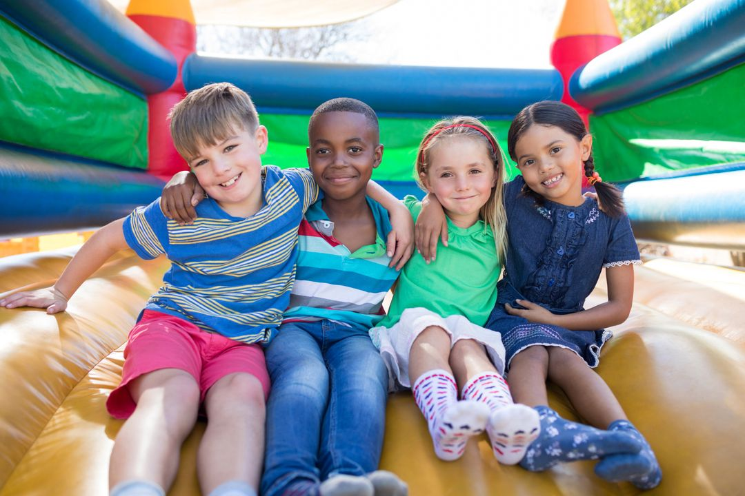 Portrait of friends with arms around sitting on bouncy castle at playground Free Stock Images from PikWizard