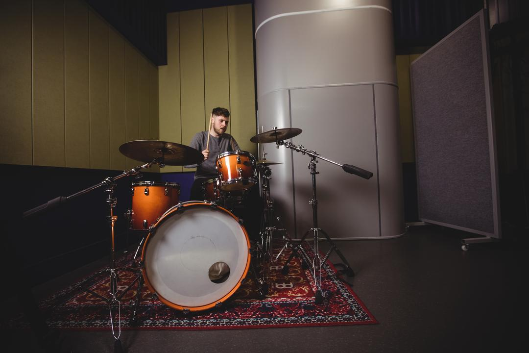 Male student playing drum set in a studio