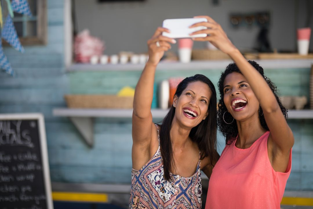 Two friends smiling taking a picture on smartphone
