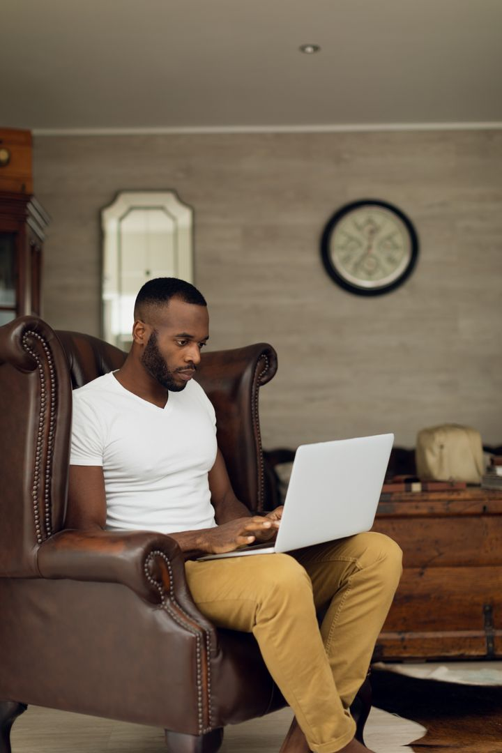 Digital composite of an African-American sitting on a leather chair inside a room while using a laptop
