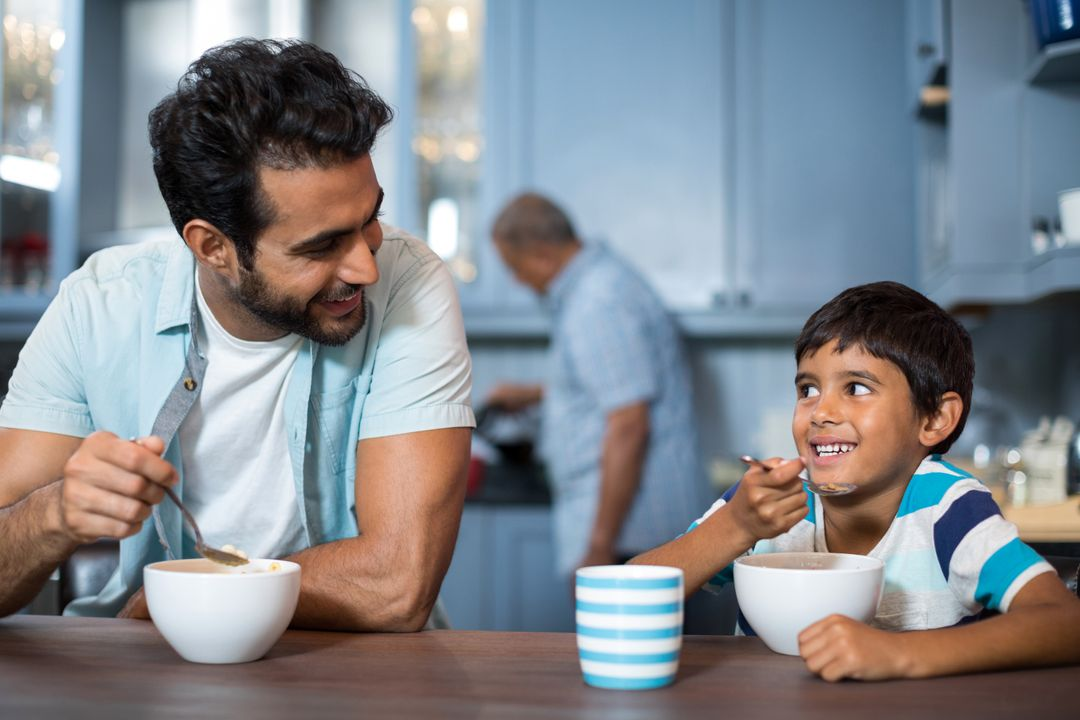 Father and son having breakfast at table with man in background Free Stock Images from PikWizard