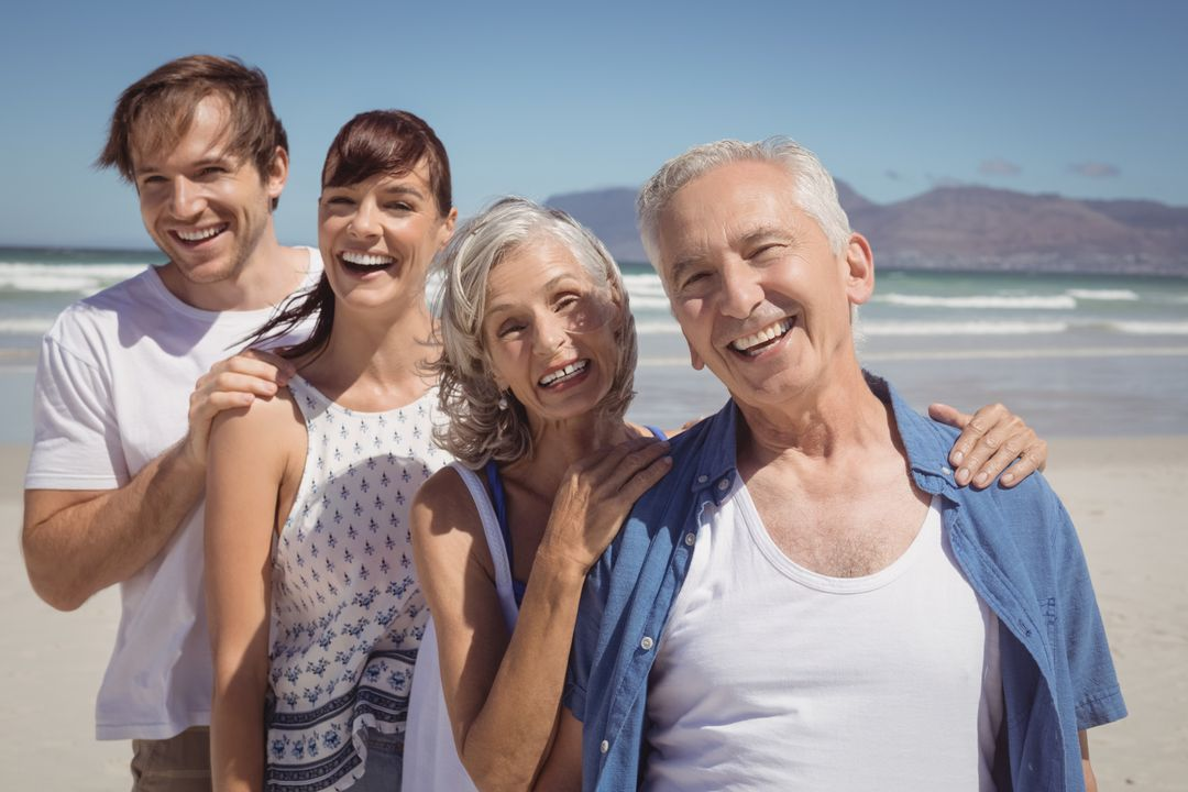 Portrait of happy family standing in row at beach during sunny day Free Stock Images from PikWizard