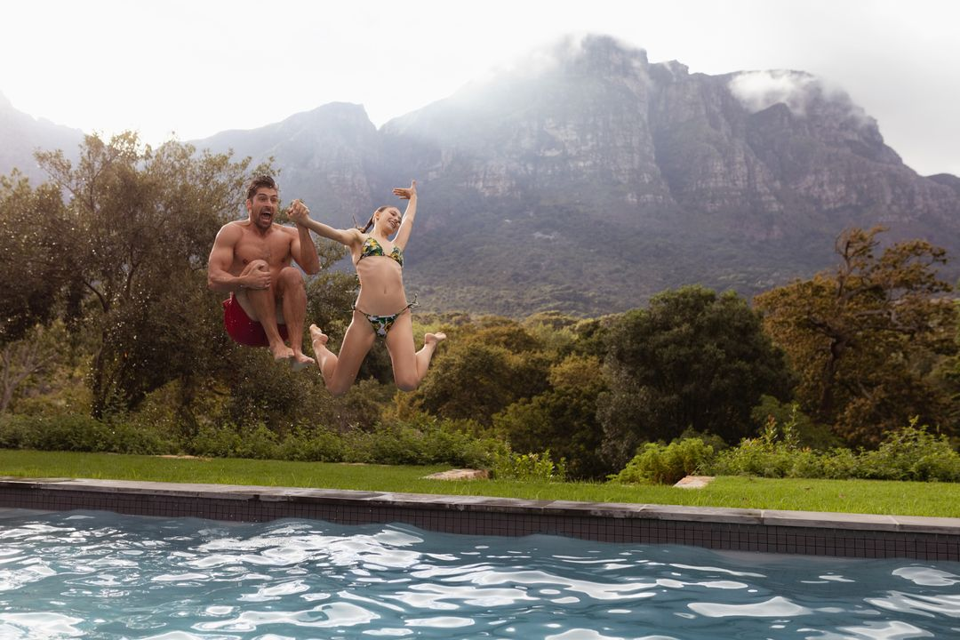 Happy couple jumping together in the swimming pool at backyard