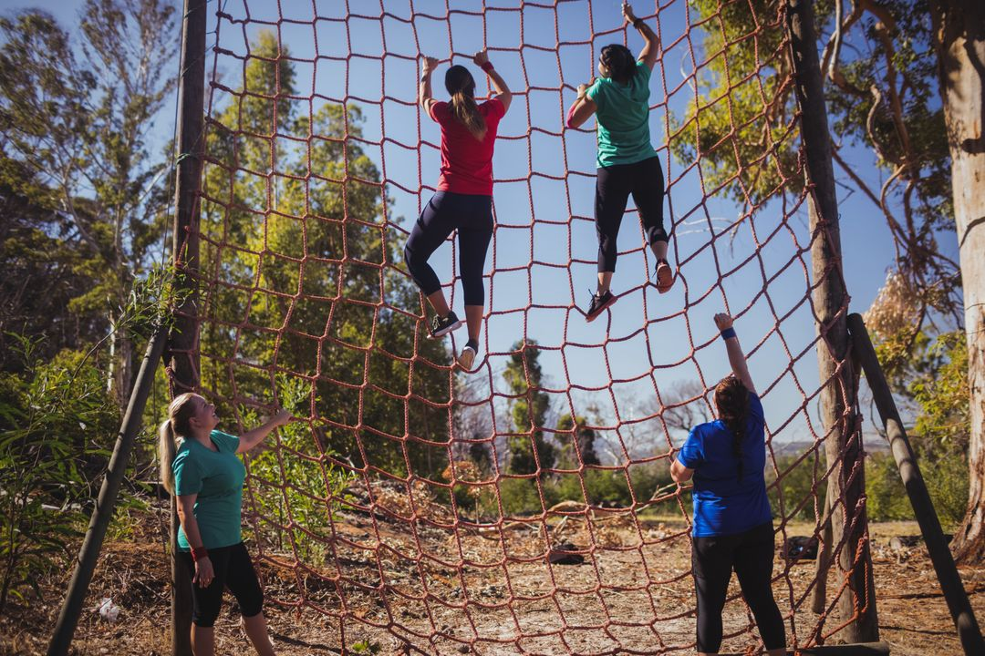 Group of fit woman climbing a net during obstacle course training in the boot camp