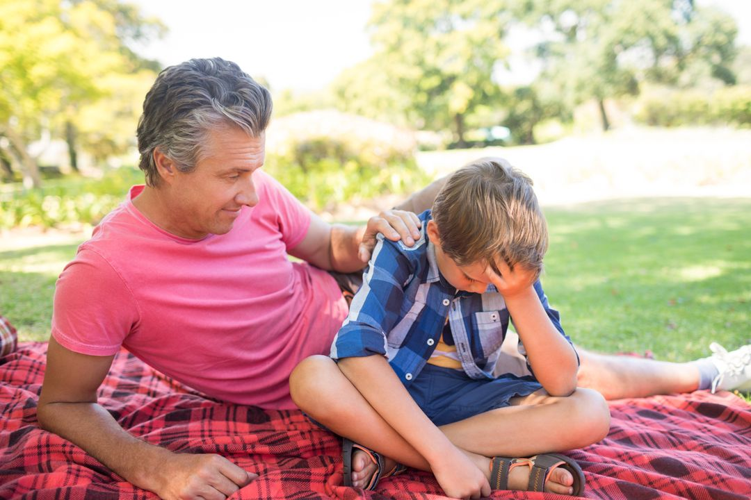 Father consoling his son at picnic in park on a sunny day Free Stock Images from PikWizard