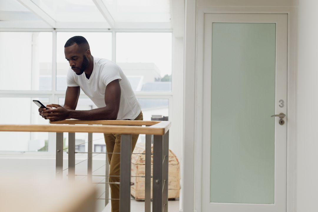 Digital composite of an African-American using a smartphone inside a white room with wood railings