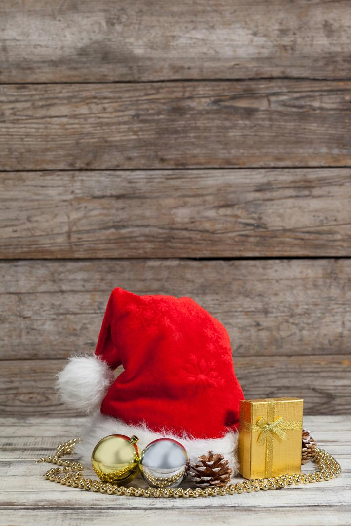 Christmas decoration, gift and santa hat kept on wooden table during Christmas time