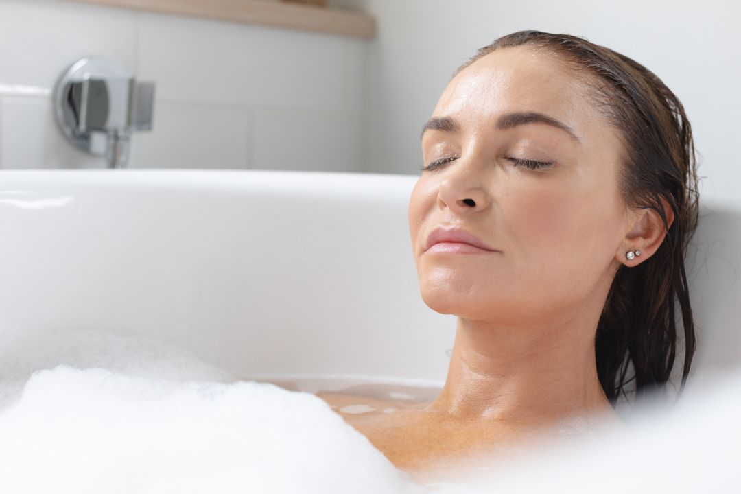 Woman relaxing in bathtub at bathroom