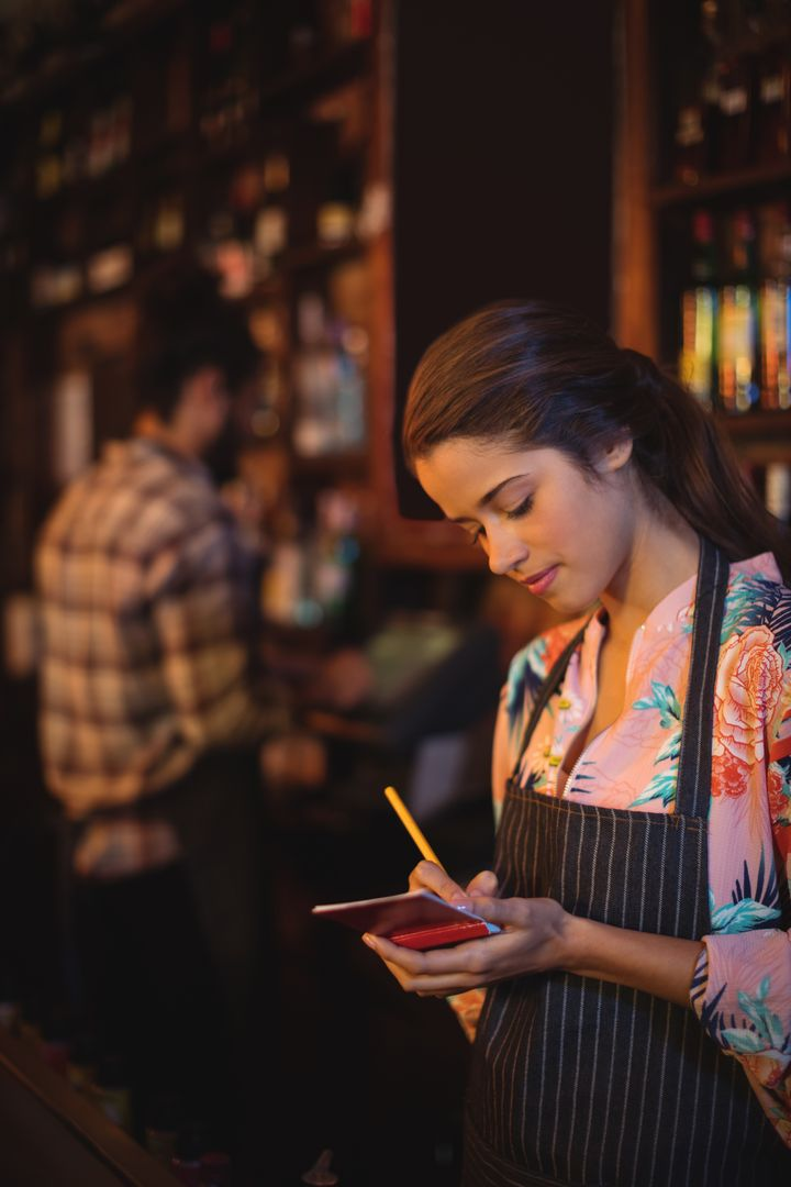 Waitress taking an order on notepad at counter in pub