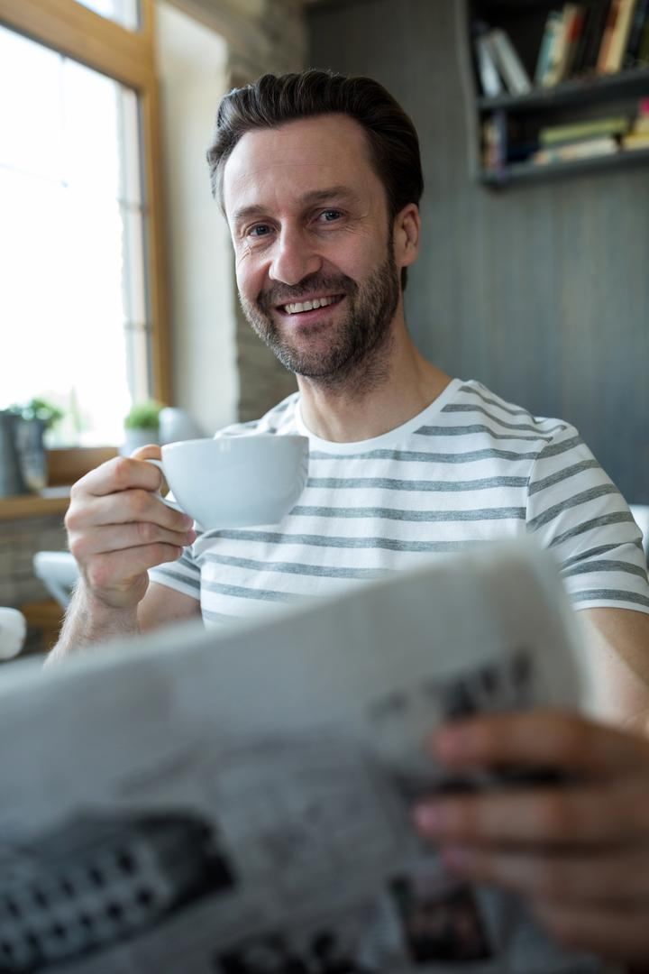 Smiling man holding a cup of coffee and reading newspaper in coffee shop