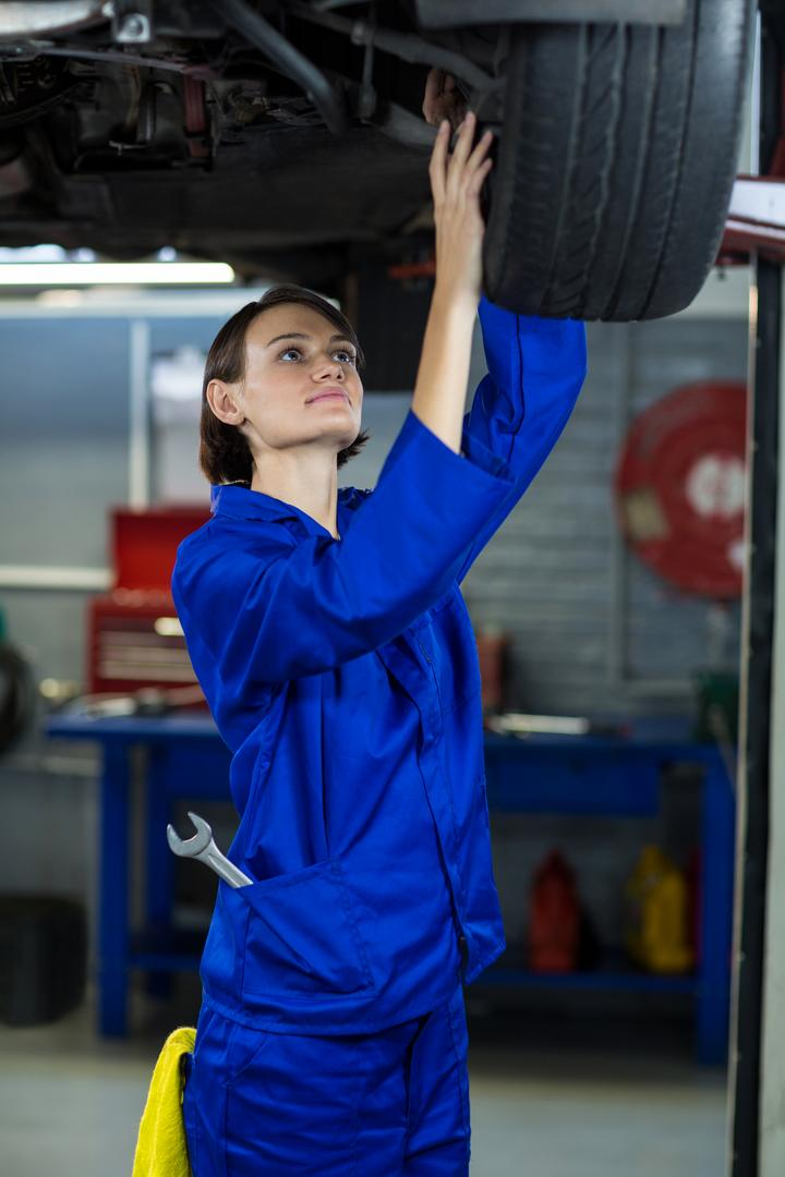 Female mechanic examining car wheel disc brake in repair garage