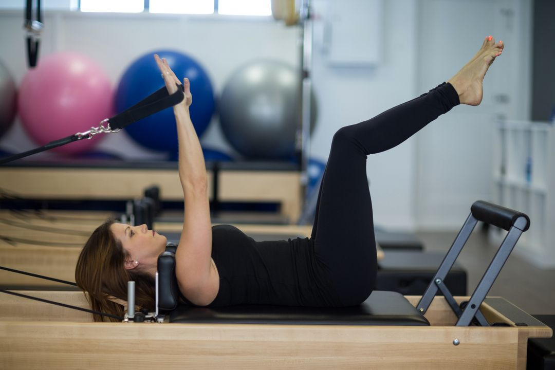 Woman practicing stretching exercise on reformer in gym Free Stock Images from PikWizard