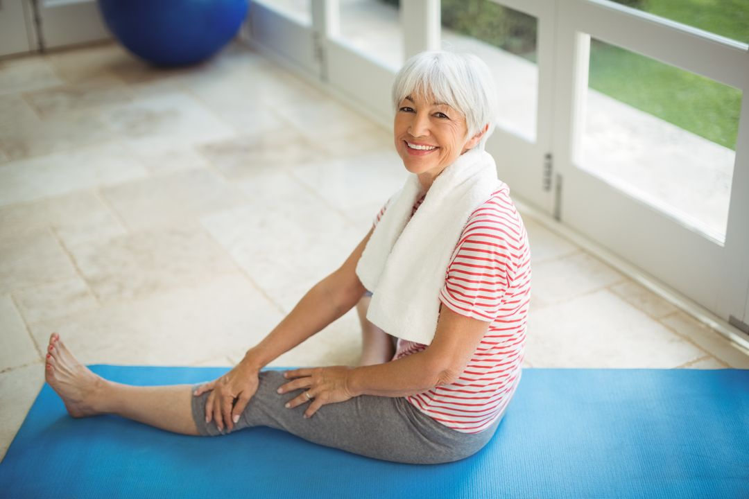 Smiling senior woman sitting with towel at home