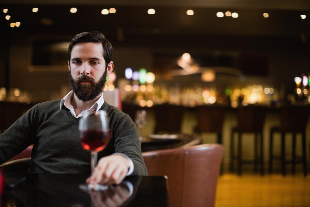 Man looking at glass of red wine in bar Free Stock Images from PikWizard