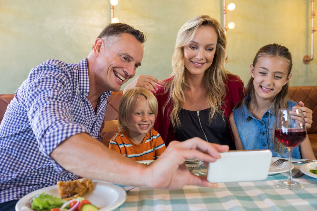 Father taking selfie with family while sitting at restaurant Free Stock Images from PikWizard