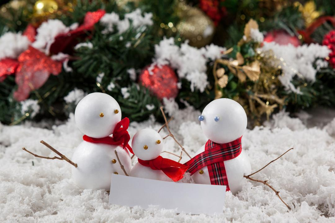 Close-up of three snowman with fake snow