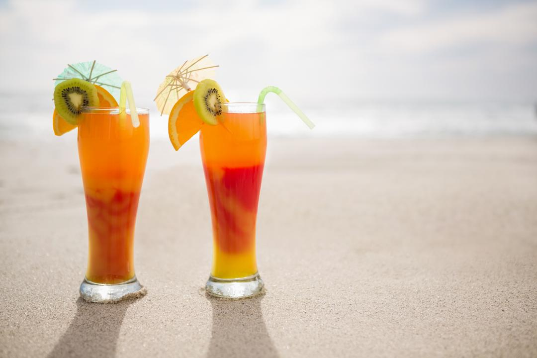 Two glasses of cocktail drink kept on sand at tropical beach