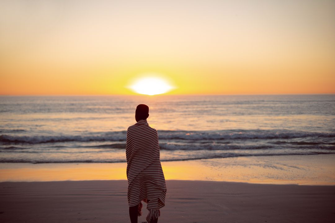 Rear view of woman wrapped in blanket standing on the beach during sunset