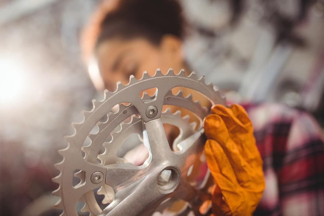 Close-up of mechanic holding a bicycle gear in workshop Free Stock Images from PikWizard