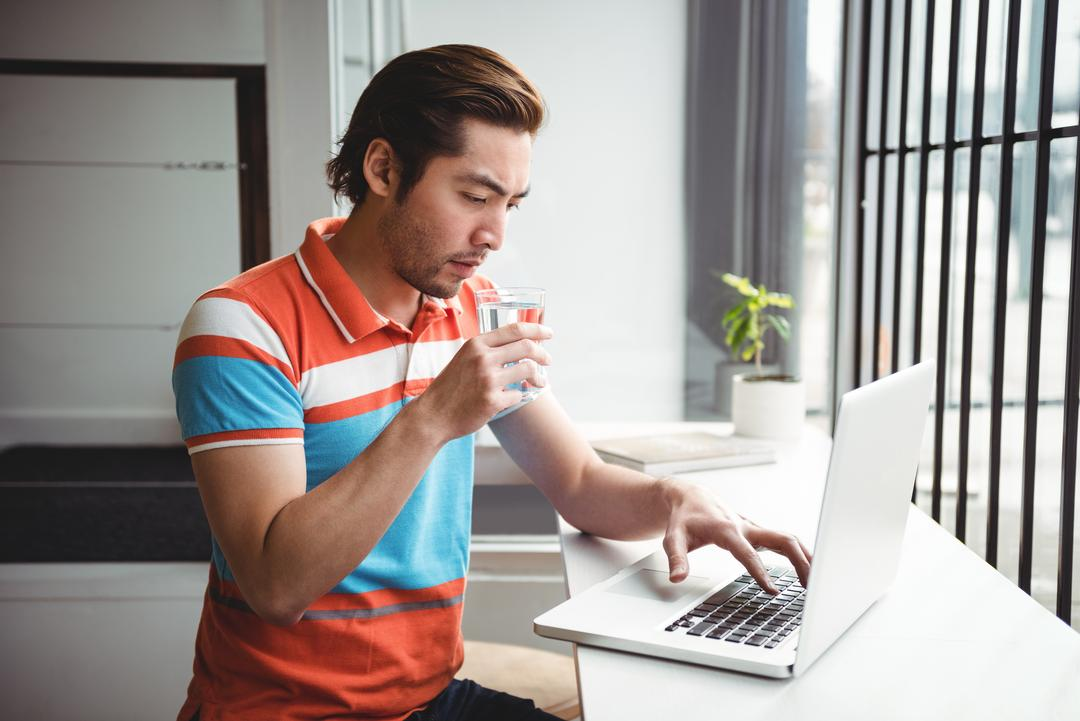 Man using laptop while drinking water in coffee shop
