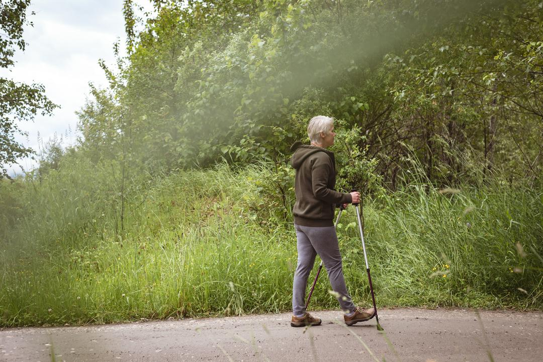 Senior woman hiker walking with hiking poles in the forest