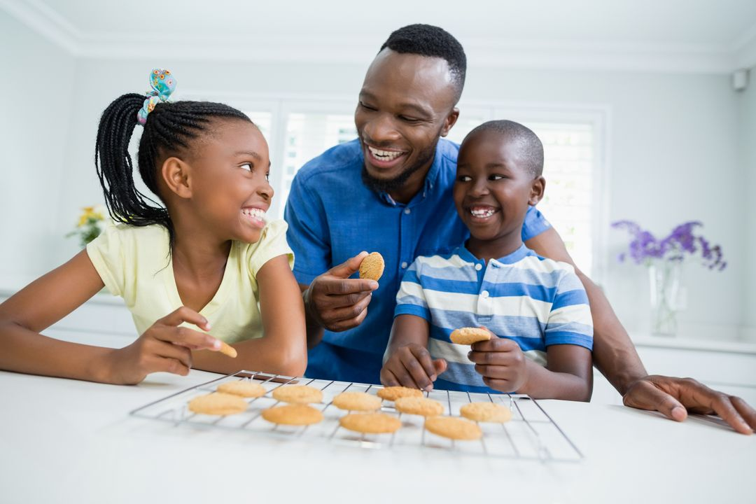 Smiling father and kids interacting while eating cookies at home Free Stock Images from PikWizard