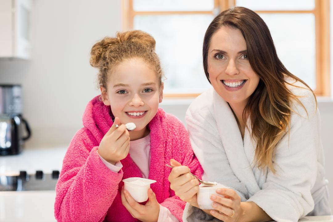 Mother and daughter eating ice cream in kitchen at home