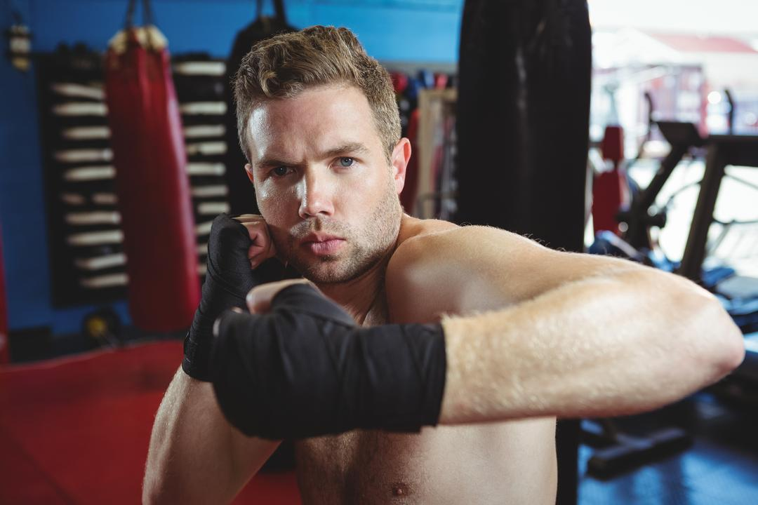 Portrait of boxer performing a boxing stance in fitness studio